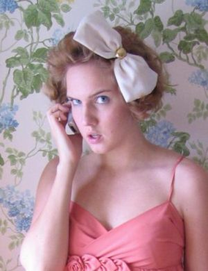 Clara i storlockig frisyr och stor rosett i håret, pratar i telefon och blänger in i kameran.