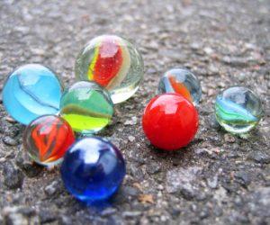 färgglada spelkulor i glas på stenig väg.