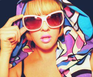 Clara i stora ljus solglasögon, rosa läppstift och en stor mönstrad och neonlysande sjal runt huvudet
