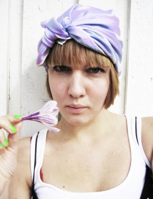 Clara vårigt klädd med lila scarf knuten som en turban om huvudet, hon håller i en nyplockad krokus i samma färg.
