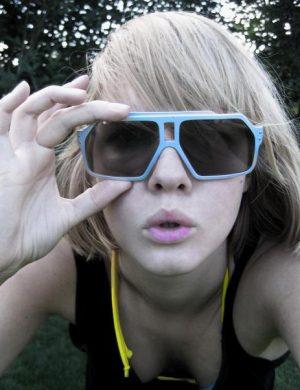 Clara i linne med gula kanter och ljusblå solglasögon som tittar mot kameran.