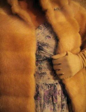 Gul fuskpäls. Clara håller ena handen i pälsen för att visa öppningen.