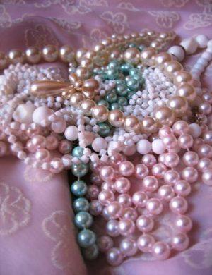 Närbild på rosa, vita och blå glimmande pärlor.