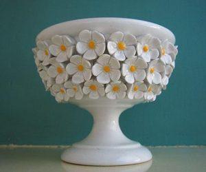 Söt liten porslinsskål i vitt med ljusa blommor som påminner om vitsippor och prästkragar.