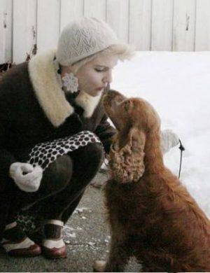Vinterklädd Clara utomhus, böjer sig ner och pussar hunden Sixten på nosen