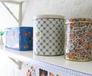 Plåtburkar i olika storlekar och färger står uppradade på liten ljus trähylla fastskruvad på köksvägg.