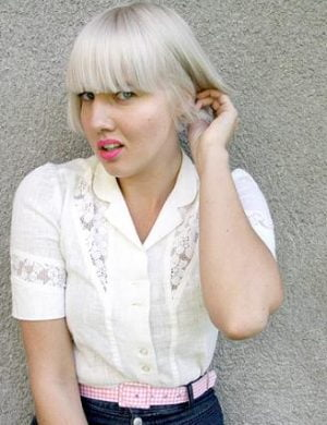 Blond Clara i page lägger hår bakom ena örat.