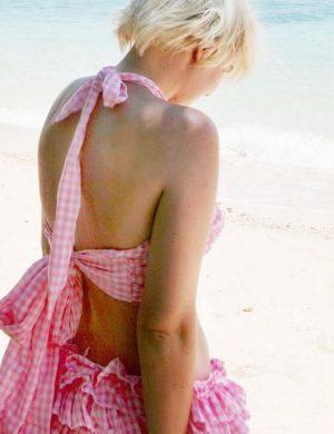 Rosarutiga sommarkläder fotat på Clara med rygg mot kameran, i nacken syns stor knuten rosett.