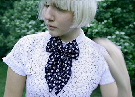 Clara i vit blus med svarta prickar, i halsen är en svart rosett knuten.