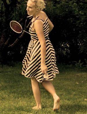 Clara spelar badminton iklädd en knälång svart och vitrandig klänning.