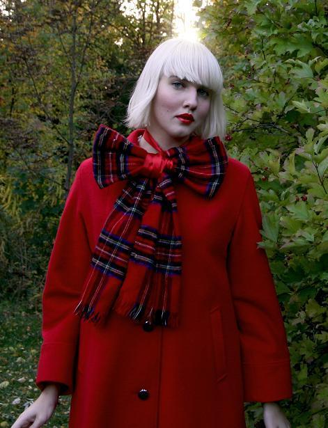 Clara klädd i djupt röd kappa och stor rutig rosett i halsen.