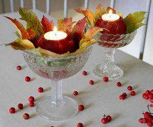 Glas på fot dekorerade med höstlöv och äpplen urgröpta för att rymma värmeljus.