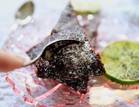 En bit krämig kladdkaka med florsocker pudrat som snö över chokladkakan. kladdkak41.jpg