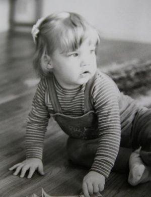 Svartvit bild på Clara som litet barn i hängselbyxor som kryper på golvet.