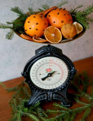 Gammeldags järnvåg med juliga apelsiner med nejlikor i vågskålen.
