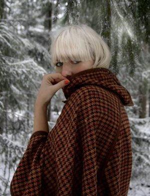 Blod Clara i page, klädd i brun rutig cape som hon döljer munnen i, ute i barrskog täckt av nysnö.