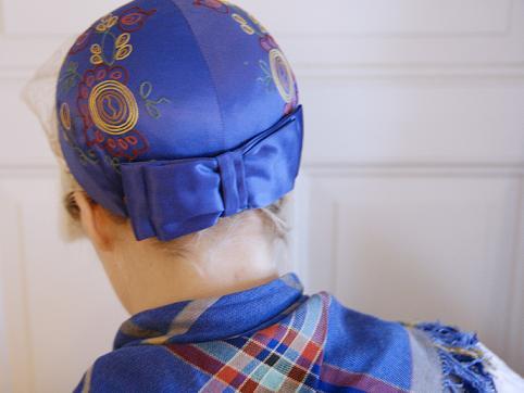 Folkdräkt med rosett i nacken på blå huvudbonad.