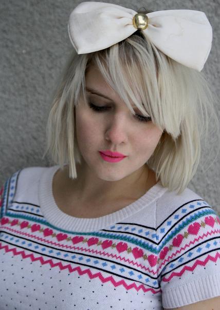 Blod Clara i färgglad jumper och vit stor rosett i håret.