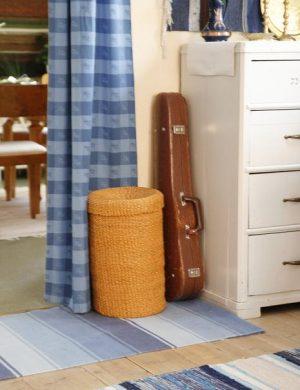 Blått draperi ovanför golv med blå trasmattor, mot väggen står ett fiolfodral lutat.