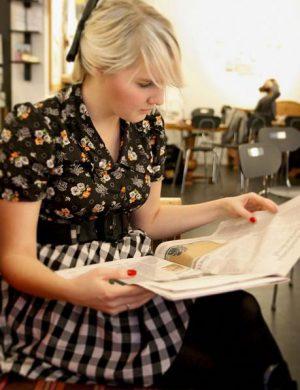 Unga blond Clara sitter i svartvit rutig kjol med uppsatt hår på café och läser tidningen.