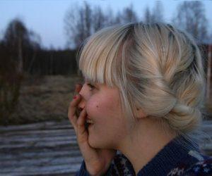 Clara i blond frisyr uppsatt som krans runt huvudet, utomhus på våren.
