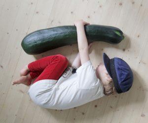 Sonen Bertil ligger på golvet med armarna om en squash som är längre än honom själv.