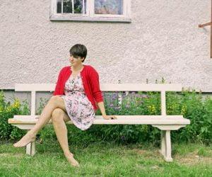 Clara i sommarklänning och röd sommarkofta sitter utomhus på ljus bänk utanför sitt hus med putsad fasad.