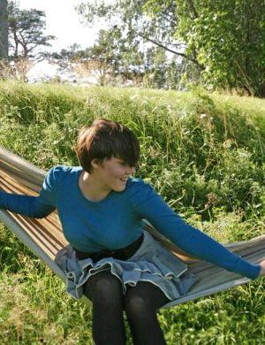 Sommarklädd Clara i mörkt hår och volangkjol sätter sig i hängmatta med äng i bakgrunden.