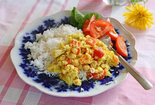 Gul färgglad currygryta som är vegetariskt på tallrik med ris och grönsaker. kikartsgryta.jpg