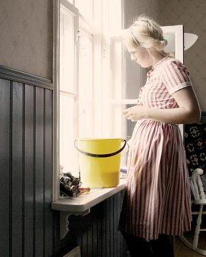 Clara putsar ett öppet vårfönster inifrån med skarp sol sol lyser på den randiga klänningen.