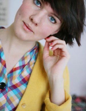 Clara i mörkt hår och gul kofta.