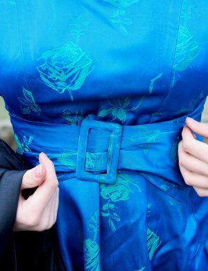 Midja som visar blå klänning med tygskärp som spänner runt glasigt tyg.