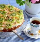 Frukttårta med kiwi och mandelspån på glasfat med fot, serverad på blårutig duk med blommig kaffekopp intill.