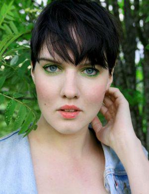 Clara i mörkt kortklippt firsyr och ögonsminkning med grön skugga i sommarväder.