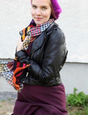 Clara i svart midjejacka, lila höstbasker och multifärgade halsdukar.