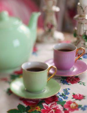 Kaffekoppar med kanna i pastellfärger dukade på blommig bordsduk.