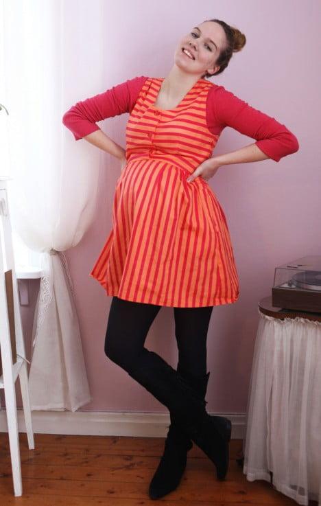 Glad Clara i rödorange klänning som täcker gravidmage, på benen mörka tighta byxor och stövlar.
