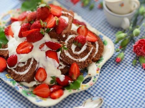 Rulltårta av choklad med grädde och färska jordgubbar.