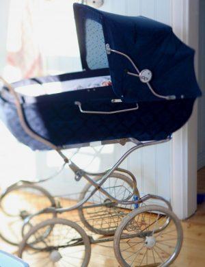 Marinblå barnvagn i gammaldags stil.