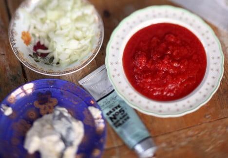 Tallrikar med ingredienser, tomatsås och lök.