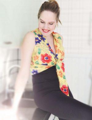 Clara i gul ärmlös och blommig knytbus, sitter på diskbänken och tittar snett ner leendes.