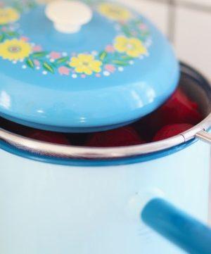 Blå emaljkastrull med blommigt lock som kokar rödbetor i sil.