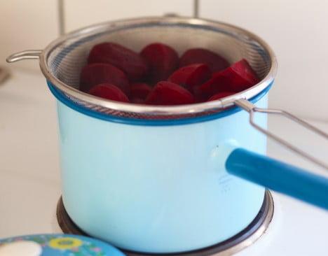 Rödbetor på väg att kokas i blåblommig kastrull på spisen.