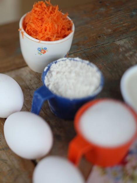 Riven morot, mjöl och ägg på bakbordet.