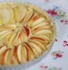Närbild på rund kaka i porslinsform där skivor av röda äpplen sticker upp ur kakan.