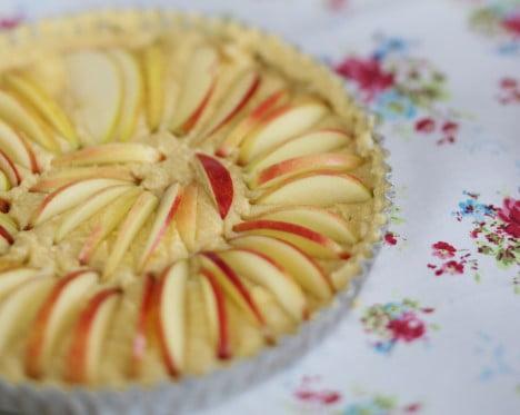Äppelskivor i mannagrynsdegen läggs i ett cirkelmönster.