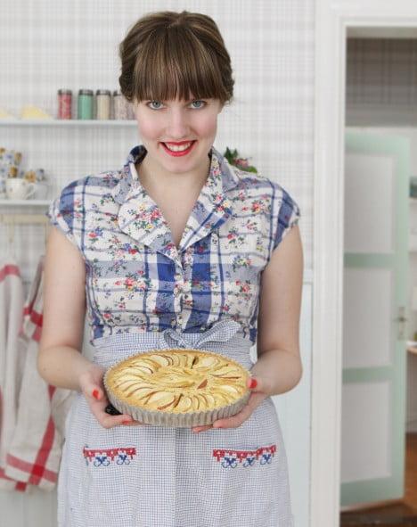 Glada bagaren med kakan av mannagryn i händerna.