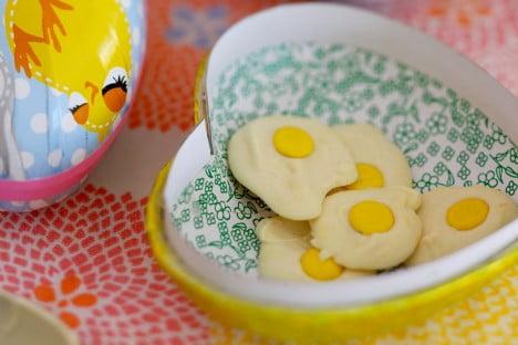 Godis som nyknäckta ägg i gult hjärtformat påskägg av papper.