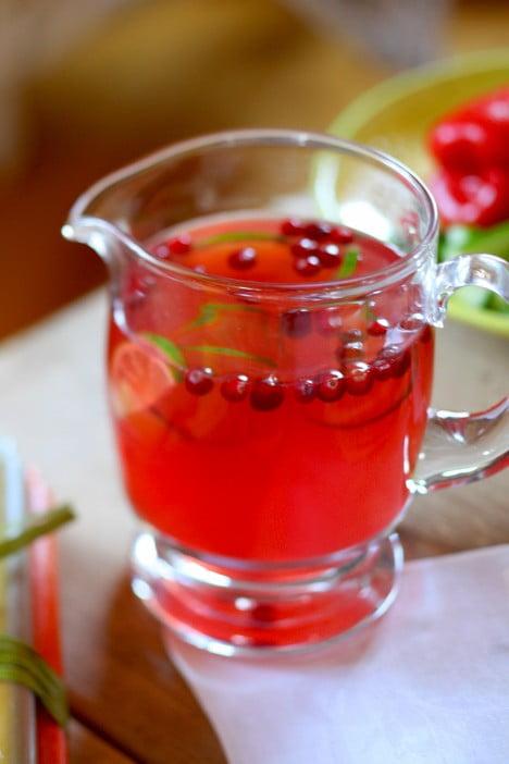 Klarröd tranbärsdricka i glaskanna.
