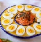 Rund tallrik med ägghalvor som ligger med gulan uppåt, i mitten kallskuren lax.